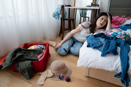 Tired asian woman sitting on floor leaning on white bed with travel suitcase clothes inside. young girl feeling bored while packing luggage hard to think what to wear for summer vacation holidays.