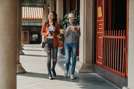 full length two asian ladies travelers walking relax in corridor in chinese temple in beijing china. best friends with camera and guide book sightseeing traditional culture in history building