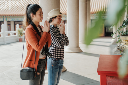 asian girls travelers pray at Buddhist temple during Chinese New Year celebration in Ho Chi Minh Vietnam. young female tourists with camera close eyes hands in hands in peaceful place outdoors. Stock Photo