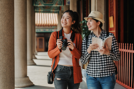 two girls tourist visiting bangkok maining attractions in thailand. women friends travel walking in corridor hallway in chinese temple on sunny day in spring. backpackers smiling with camera and book