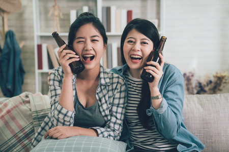 Group happy young female people sitting on sofa with bottled drinks. two asian girl best friends holding beers putting by cheeks face camera laughing smiling attractive sitting on couch at home. 免版税图像