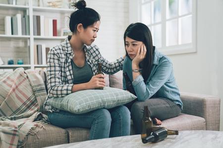 Joven mujer asiática consolando a su amigo deprimido en la sala de estar en casa mientras está sentado en el cómodo sofá del sofá. dos chicas molestas hablando con botellas de cerveza y bebidas en la mesa. mujer desgarradora. Foto de archivo
