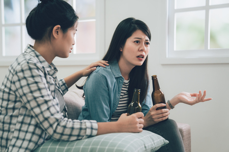 asian woman complaining telling to friend about her problems sitting on couch sofa at home. two girls holding bottle of beers drinking. roommate concentrated listening to lady and comforting her. Stock Photo