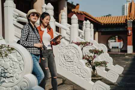 happy smiling asian women visit chinese history monument with guide book.