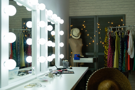 Decorative cosmetics and tools on dressing table with bright mirror in makeup room.
