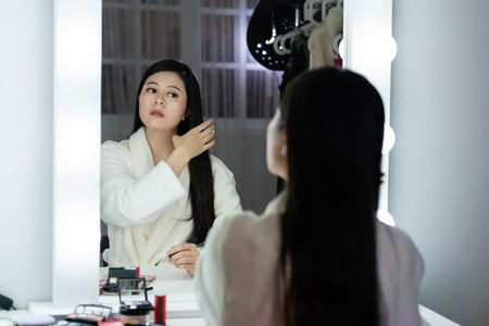 popular chinese female superstar sitting in dressing room and light in studio backstage.