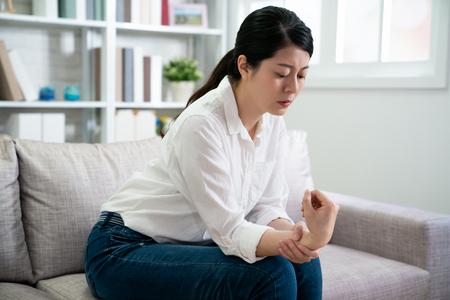 Sindrome da ufficio dolore alla mano da malattia professionale. Chiuda sulla donna di affari asiatica con il polso ferito dopo il lavoro a casa.