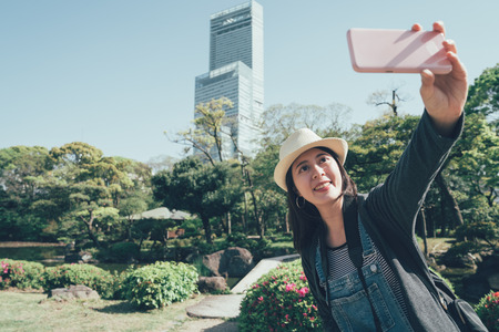 Travel and life style concept. beautiful lady with hat holding mobile phone take selfie in garden Stock Photo