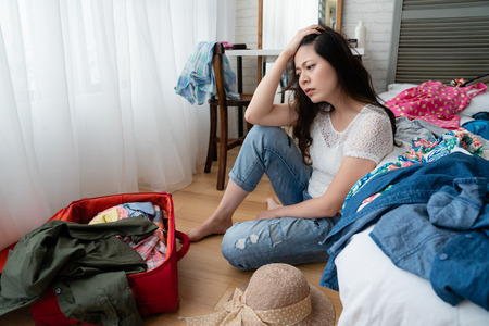 Young unhappy asian woman with suitcase sits on wooden floor in bedroom.