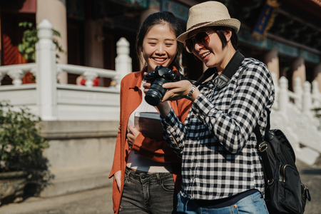 two happy smiling women travelers standing at chinese temple and white marble stone railings in back。 Stock Photo