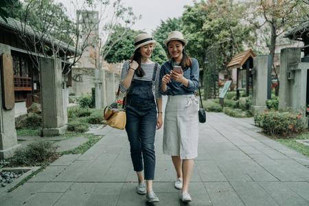 Lächelnde glückliche junge Freundinnen, die Reisende auf dem alten Straßenweg spazieren, der von einem japanischen traditionellen Geschäft umgeben ist.