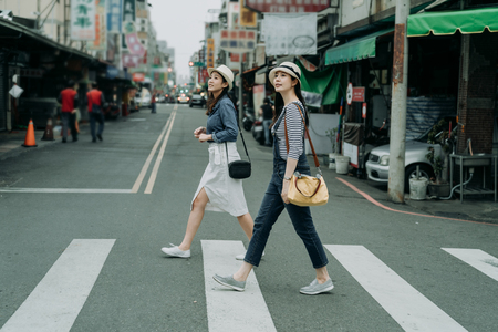 two happy female friends travelers with bags crossing street together outdoor sunny day in china town.