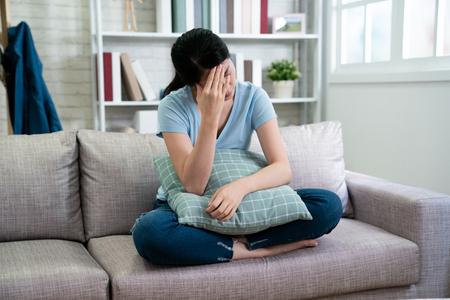 estrés dolor de cabeza concepto de salud y personas. infeliz mujer asiática ama de casa con dolor de cabeza de ojos cerrados sentado en el sofá contra la ventana en la acogedora sala de estar en casa. Foto de archivo