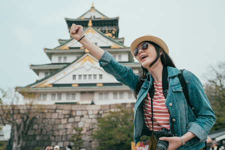 Confident young asian woman tourist raising fist up in blue sky.