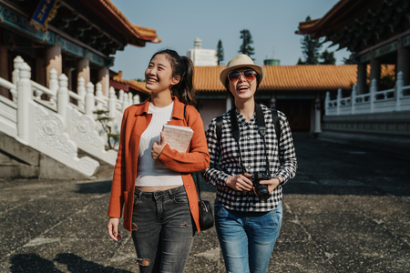 Travel tourist frienship. two smiling girls backpackers walking in chinese confucius temple in beijing china.