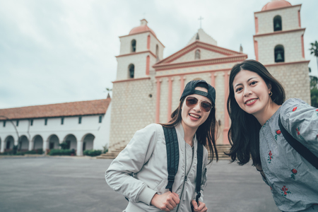 two asian friends take selfie with Old Mission Santa Barbara while travel america. Stock Photo