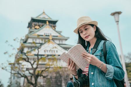 elegant female traveler looking on paper book. Stock Photo