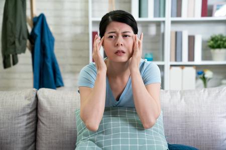 Concepto de dolor de cabeza. ama de casa mujer asiática enferma sentada en el sofá interior.