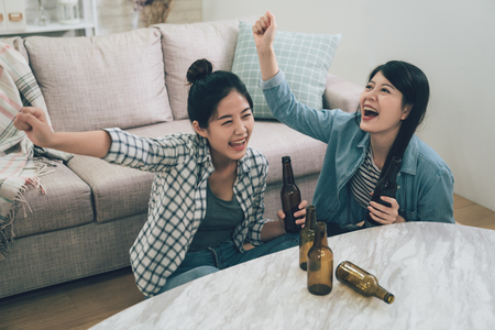 two female happy friends watching soccer on tv and celebrating victory at home. Archivio Fotografico