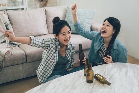 twee vrouwelijke gelukkige vrienden die voetbal op tv kijken en de overwinning thuis vieren.