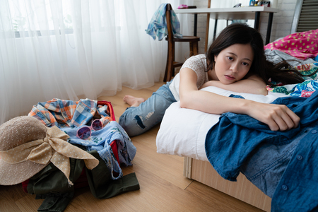 frustrated woman packing luggage in bedroom relaxing on bed with unhappy emotion. Stock Photo
