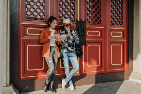 full length of happy beautiful asian women travelers leaning on wall of chinese temple and discussing. Stock Photo