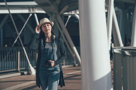 asian smiling elegant woman walking on Footbridge. Stock Photo
