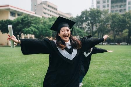 szczęśliwe azjatyckie studentki w deskach z zaprawy murarskiej i kawalerskich sukniach z okazji udanego ukończenia szkoły.