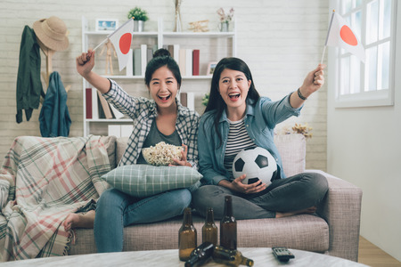 cheerful girls friends with japan flag cheer up on games sitting on couch sofa.