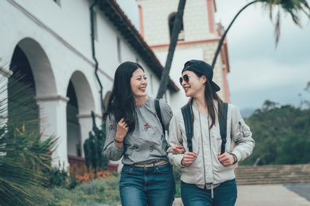 two happy female friends walking together outdoor in city sightseeing Old Mission Santa Barbara. Stock Photo