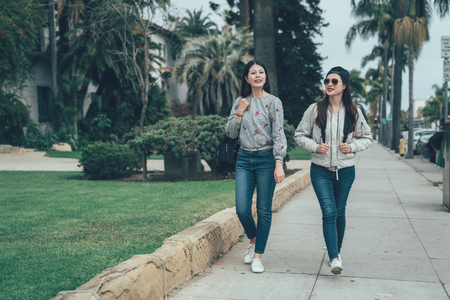 full length of young asian girl backpackers walking on street outdoor by trees along road in Santa Barbara County Courthouse. two beautiful college students after school talking back to home. Stock Photo