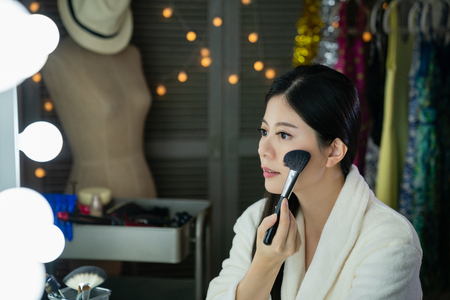 side view of beautiful chinese host doing make up in backstage looking in mirror. young asian entertainer woman applying dry cosmetic tonal foundation on the face using makeup brush in dressing room. Stock Photo