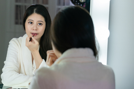Beautiful asian woman artist makeup applied red lipstick by brush. japanese young beauty model girl wearing bathrobe painting lips looking at mirror in dressing room backstage. singer get ready.