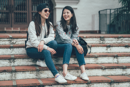 Two cheerful asian girls talking and sitting on stairs in street Santa Barbara County Courthouse. concept of sincere friendship travel together lifestyle. female college students laughing joyful.
