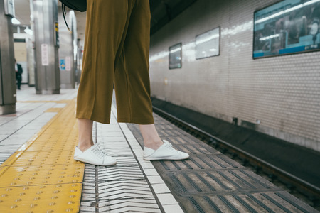 asian female woman feet in white sneakers crossed approach the line in subway platform. dangerous not safe