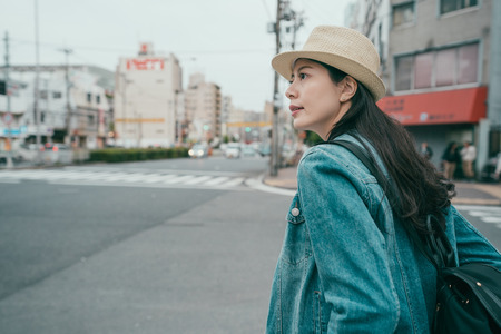 young smiling traveler woman in hat with backpack standing on crosswalk in osaka city street. Stock Photo