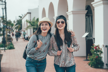 two asian girl tourist smiling walking on street shopping while travel in santa barbara america.
