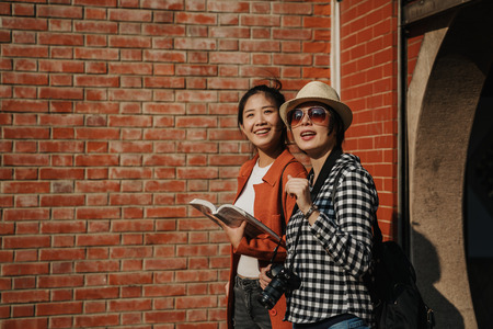 two fashion asian women in sunglasses and camera walking out a chinese temple by red brick wall behind.