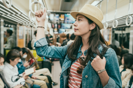 young female asian traveler hand holding handle standing on subway train.