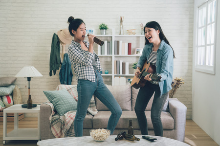 Young happy girl best friends having party together by playing guitar and another singing by holding beer bottle as microphone.