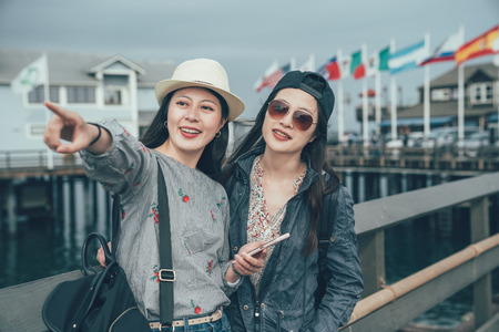 two happy asian women travel backpacker smiling and showing friend amazing ocean scenery while sightseeing in Stearns Wharf in Santa Barbara California usa.