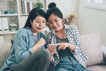 Front view portrait of two joyful asian female friends listening music in living room at home.