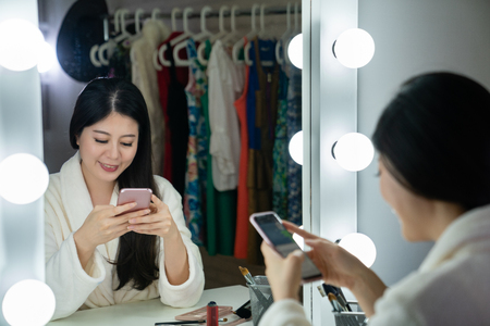 back view of young korean actress sitting in front of light mirror looks joyfully on cellphone in backstage.
