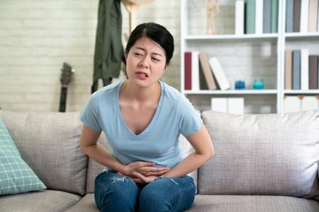 asian chinese woman having painful stomachache.