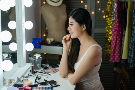 side view of young chinese model looking mirror practicing pose while applying makeup in backstage.