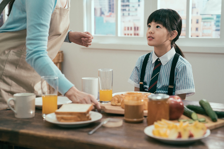 unrecognized mom in apron standing at wooden table with healthy meal. Stok Fotoğraf