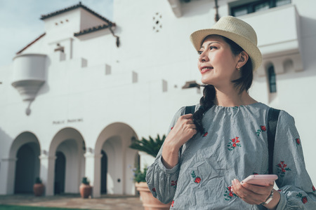 elegant asian woman traveler with straw hat and mobile phone standing outdoor on sunny day with white traditional style building in background.