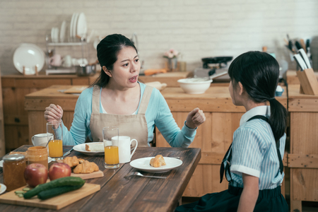 lazy sleepy little girl wake up late for school sitting at kitchen table with breakfast at home. frowning angry mom loudly nag at daughter bad habit in early morning. unhappy asian mother worried.