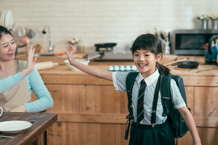 elegant smiling mother in apron saying goodbye to children as leave home for elementary school. little girl daughter in uniform walking after breakfast in kitchen carry heavy backpack bag waving hand