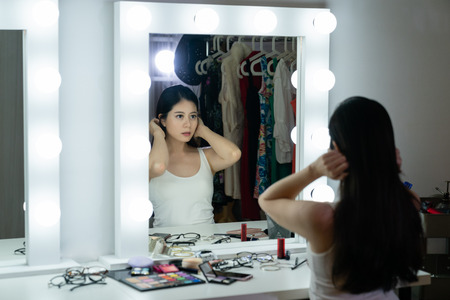 pretty young sensual japanese model woman with beautiful makeup and elegant hairstyle looking at her reflection in mirror and fixing hair in backstage. asian beauty fashion and make up dressing room Stock Photo